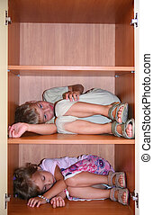 Two children sleeps on shelves in cabinet