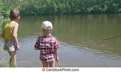 Two children stand on the river Bank. In the hands of children rods. Hot summer day.
