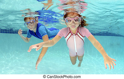 two children swimming underwater in pool