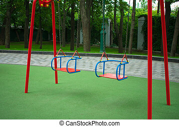 Two children swing in the park.