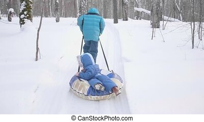 Two children walk in the winter Park. Riding in a sleigh. Outdoor activities and walking