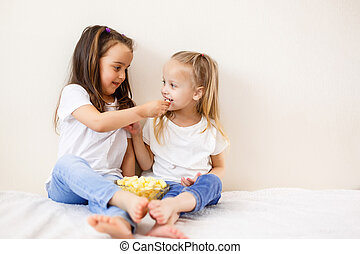 Two children with popcorn against the white background