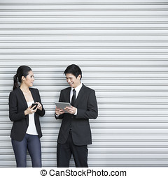 Two Chinese business colleagues using tech device's