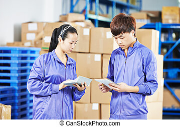 two chinese female workers in warehouse - two young chinese...