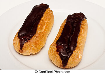 Two Chocolate Covered Eclairs on a White Plate