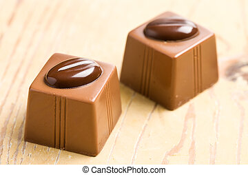 two chocolate pralines on wooden table