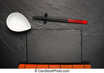 Two chopsticks and white bowl on black stone background with copyspace, top view