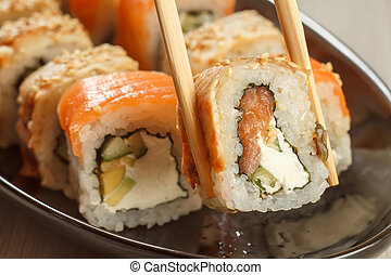 Two chopsticks holding Uramaki sushi roll with Conger
