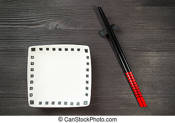 Two chopsticks on wooden background