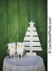 Two Christmas owls on a table near a decorative Christmas tree on a green background. New year greeting card template. Christmas mock up.
