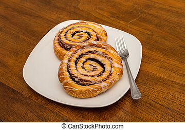 Two Cinnamon Rolls on White Plate with Fork