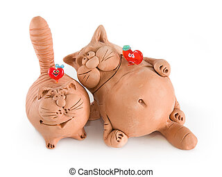 Two clay funny cats with two glass hearts isolated on white...