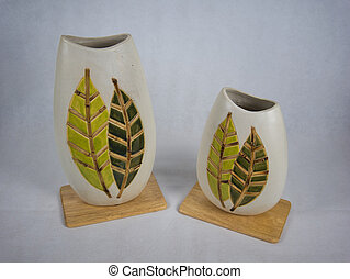 Two clay vases with pattern on a wooden board
