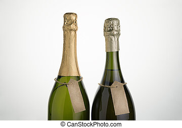 Two clear bottles of sparkling wine on a light background.