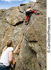 Two climbers - A female belaying a male on a steep rock face...
