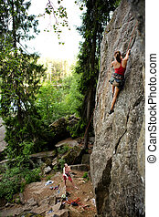 Two climbers - A female climber, climbing using a top rope ...