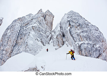 Two climbers approach to a winter steep face - Two climbers...
