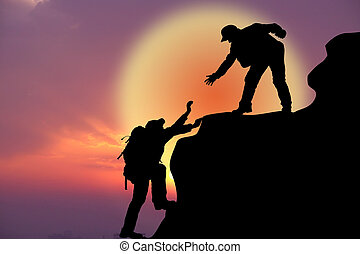 Two climbers climb uphill against the sky
