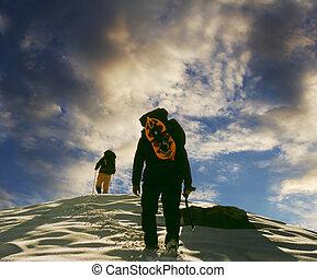 Two climbers the climb on the peak