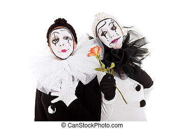 two clowns, one gives a flower to the other