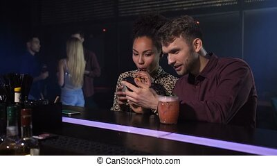 Handsome man networking online on smartphone with curly dark-skinned female colleague in modern fusion bar. Mixed race co-workers enjoying after-work leisure, cocktail drinks, streaming on cellphone