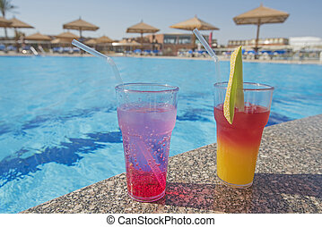 Two cocktail drinks by a tropical swimming pool