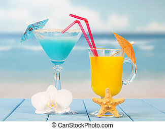 Two cocktails with umbrellas close up on background of the sea