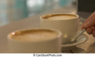 Two coffee cup on table in cafeteria close up. Cups with...