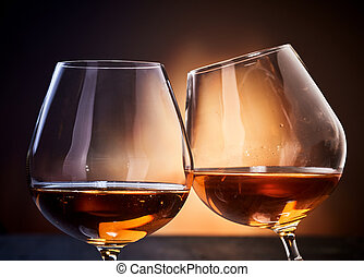 Two cognac glasses clinking