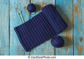 Two coils of wool, knitting needles and a blue knitted scarf