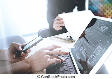 two colleague web designer discussing data and digital tablet docking keyboard and computer laptop with smart phone and design diagram on marble desk, sun light effect
