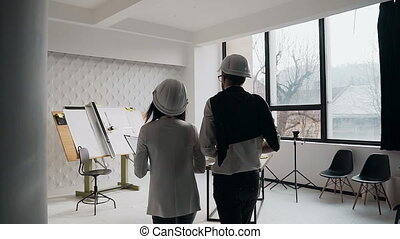 Two colleagues - a man and a woman go to a drawing device who stand near the white wall on the construction site