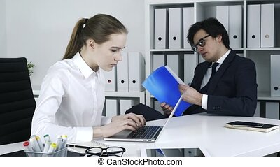 Two colleagues are checking details at laptop and prepared notes.
