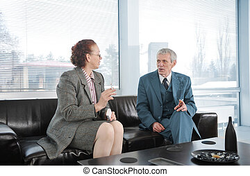 Two colleagues having a break during business meeting with cigarette