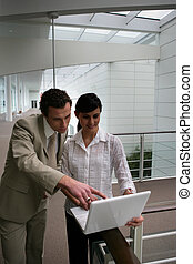 Two colleagues having meeting in corridor