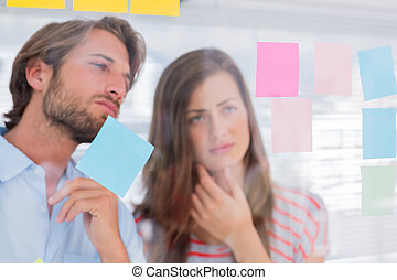 Two colleagues looking at sticky notes
