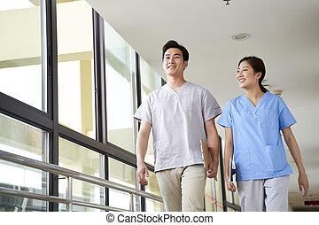 two colleagues of nursing home walking in hallway