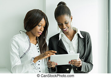 Two colleagues talking about the contents on a tablet pc in a well lit office close to the window