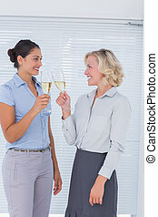 Two colleagues toasting with champagne