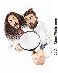 Two colleagues using a magnifying glass