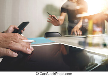 two colleagues web designer discussing data and blank screen digital tablet and computer laptop with smart phone on wooden desk as concept