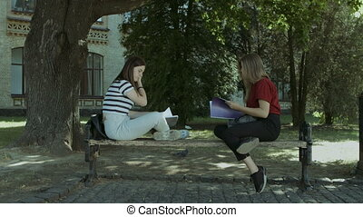 Two college girls talking on the bench after study