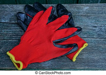 two colored construction gloves on a gray wooden board