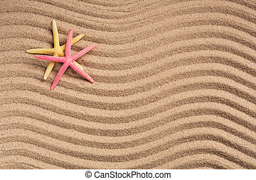 Two colored starfish on a summer beach on textured sand. Summer background. Photo for banner or advertisement. Top view.