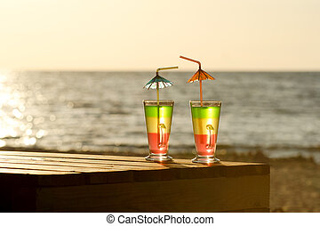 Two colorful cocktails in the morning sun on a wooden table on the beach against the sea