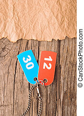 two colorful tags with numbers on old paper