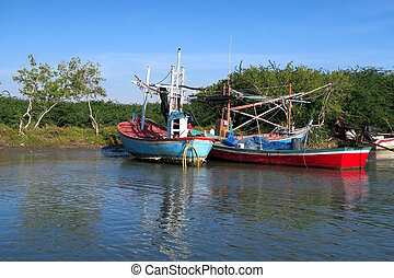 Two colorful traditional fishing boats on a river