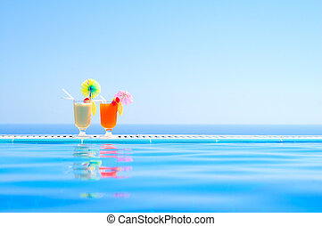Two Colorful Tropical Cocktails near the Swimming Pool on Background of Warm Blue Sea. Exotic Summer Vacation.