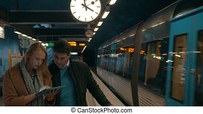 Two commuters using tablet PC at metro station