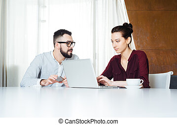 Two concentrated businesspeople working with laptop in meeting room
